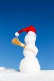 Boneco de neve com um tampão aguçado e uma vassoura na neve Fotografia de Stock
