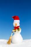 Boneco de neve com um tampão vermelho e uma vassoura na neve Fotos de Stock Royalty Free