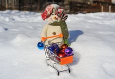 Boneco de neve com um trole do supermercado pequeno Fotografia de Stock