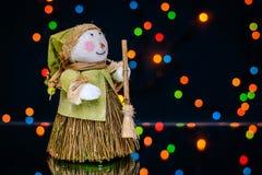 Boneco de neve com uma vassoura em um fundo de luzes coloridas Imagem de Stock