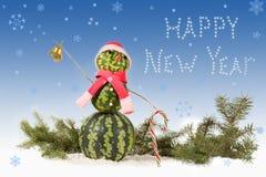 boneco de neve da melancia no chapéu e no lenço vermelhos com o bastão de doces no fundo azul e em flocos de neve de queda Fotos de Stock