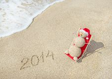 Boneco de neve de Sandy no banho de sol do chapéu de Santa na sala de estar da praia Fotografia de Stock
