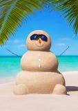 Boneco de neve de Sandy nos óculos de sol no oceano ensolarado tropical Palm Beach Fotografia de Stock