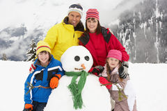 Boneco de neve do edifício da família no feriado do esqui Imagem de Stock