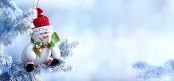 Boneco de neve do Natal que pendura em um ramo de árvore da neve Foto de Stock Royalty Free