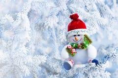 Boneco de neve do Natal que pendura em um ramo de árvore da neve Foto de Stock