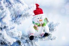 Boneco de neve do Natal que pendura em um ramo de árvore da neve Fotos de Stock Royalty Free
