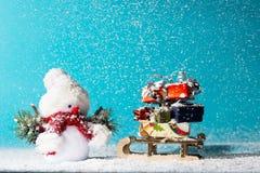 Boneco de neve e pequeno trenó com os presentes do Natal no fundo ciano fotografia de stock