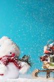 Boneco de neve e pequeno trenó com os presentes do Natal no fundo ciano fotografia de stock royalty free