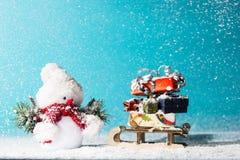 Boneco de neve e pequeno trenó com os presentes do Natal no fundo ciano fotos de stock