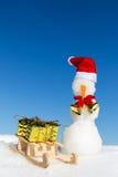 Boneco de neve e um pequeno trenó com os presentes na neve Foto de Stock Royalty Free