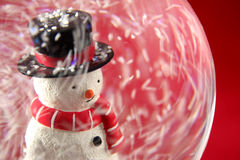 Boneco de neve em Snowglobe com fundo vermelho fotos de stock royalty free