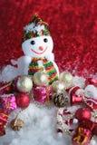 Boneco de neve em um fundo vermelho e neve com bolas brilhantes jpg Imagem de Stock
