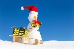 Boneco de neve engraçado e um pequeno trenó com presentes na neve Fotografia de Stock Royalty Free