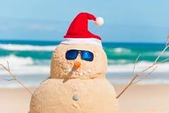 Boneco de neve feito fora da areia com chapéu de Santa Fotografia de Stock