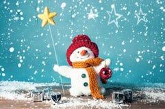 Boneco de neve pequeno com estrela e presentes Foto de Stock