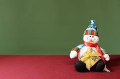 Boneco de neve que guarda um presente dos anos novos Fotografia de Stock Royalty Free