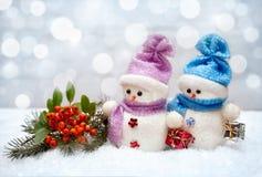Bonecos de neve com caixas de presente pequenas e ramo com bagas vermelhas Foto de Stock Royalty Free