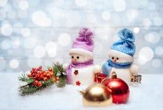 Bonecos de neve com ramo com bagas e as bolas vermelhas do Natal Imagens de Stock