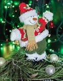 Bonecos de neve em um tampão vermelho no pinho verde Fotografia de Stock