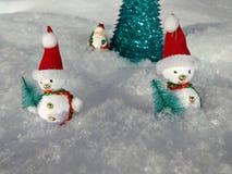 Bonecos de neve perto da árvore de Natal artificial na neve Fotografia de Stock