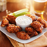Boneless buffalo bbq chicken wngs with ranch sauce and beer. Bathed in warm light royalty free stock photo