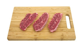 Boneless top blade steak on cutting board Stock Photos