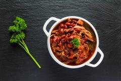 Bonen met varkensvlees in kruidige tomatensaus met ui, paprika, bier, klok en roze peper wordt gestoofd die Royalty-vrije Stock Afbeeldingen