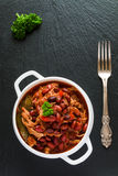 Bonen met varkensvlees in kruidige tomatensaus met ui, paprika, bier, klok en roze peper wordt gestoofd die Royalty-vrije Stock Foto