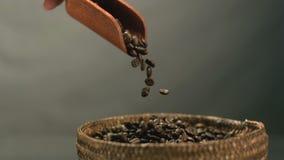 Bonen van de hand de gietende koffie van een houten lepel in mand stock video