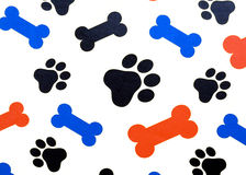 Bones and Paws. Colorful dog treat bones and paw prints over a white background Royalty Free Stock Photos