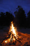 Bonfire. A large flaming bonfire in the sand in the evening royalty free stock photos