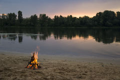 Bonfire on the bank of the river at sunset Stock Image