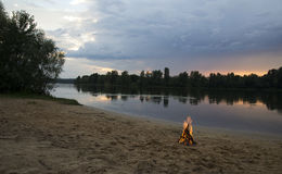 Bonfire on the bank of the river at sunset Stock Photos