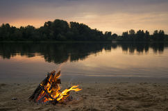 Bonfire on the bank of the river at sunset Royalty Free Stock Images