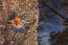Bonfire on the banks of the creek in the spring forest. View from above royalty free stock image