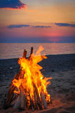 Bonfire on the beach by the sea at sunset Stock Photography