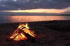 Bonfire burning on the riverbank  on the sunset. Ob river, Siberia, Russia Stock Photos