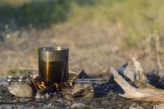 Bonfire while camping in the spring. At the stake water boils in stock photography