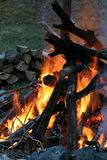 Bonfire at Dusk. Large bonfire at Dusk with firewood in background royalty free stock image