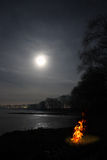 Bonfire flame and moon over lake Stock Photos
