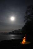 Bonfire flame and moon over lake stock photos