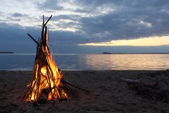 Bonfire in the form of a tent burning on the riverbank  on sunset Royalty Free Stock Images