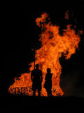 Bonfire III. Silhouettes of people against large bonfire at night stock images