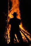 Bonfire. Men watching wood bonfire in the wilderness Stock Image