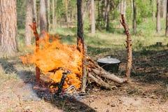 Bonfire next to the tourist camp. Journey into the wild concept. Stock Photos
