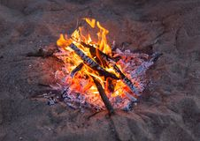 Bonfire sand a bright flame in the evening. Holidays on the barbecue picnic at the beach Royalty Free Stock Image