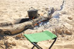 Bonfire and tourist bowlers with cooking food on the beach background.  royalty free stock photography