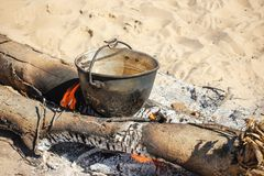 Bonfire and tourist bowlers with cooking food on the beach background.  stock image