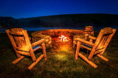Bonfire. Two empty chairs by the firepit near a lake at night Royalty Free Stock Images
